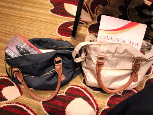 Similar bags, terrible carpet. Two purses next to each other, stuffed with conference paraphernalia.