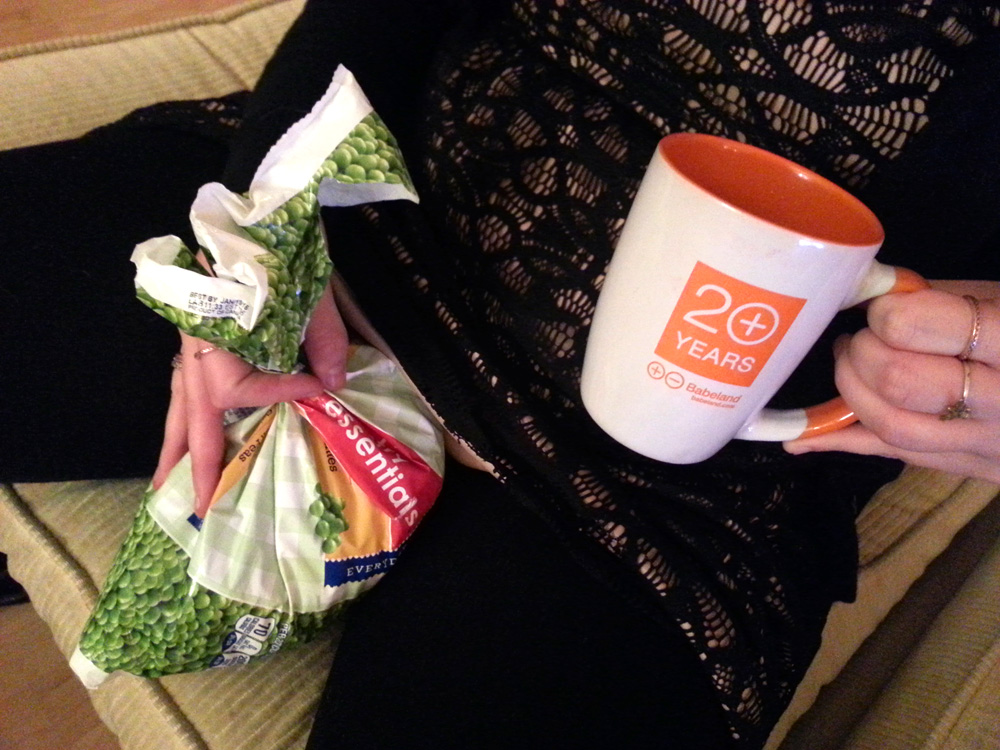 Queeraschino holding a bag of peas to her crotch while holding a Babeland mug.