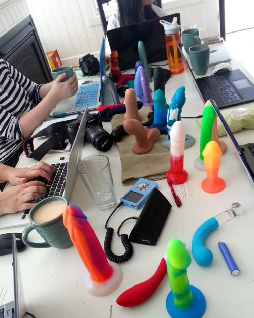 Bloggers around a big table, with their laptops out and surrounded by dildos.