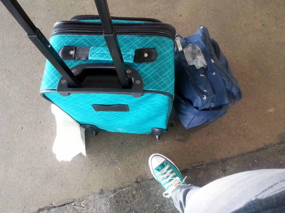 Waiting for the shuttle at the airport with my turquoise suitcase and turquoise Converse.
