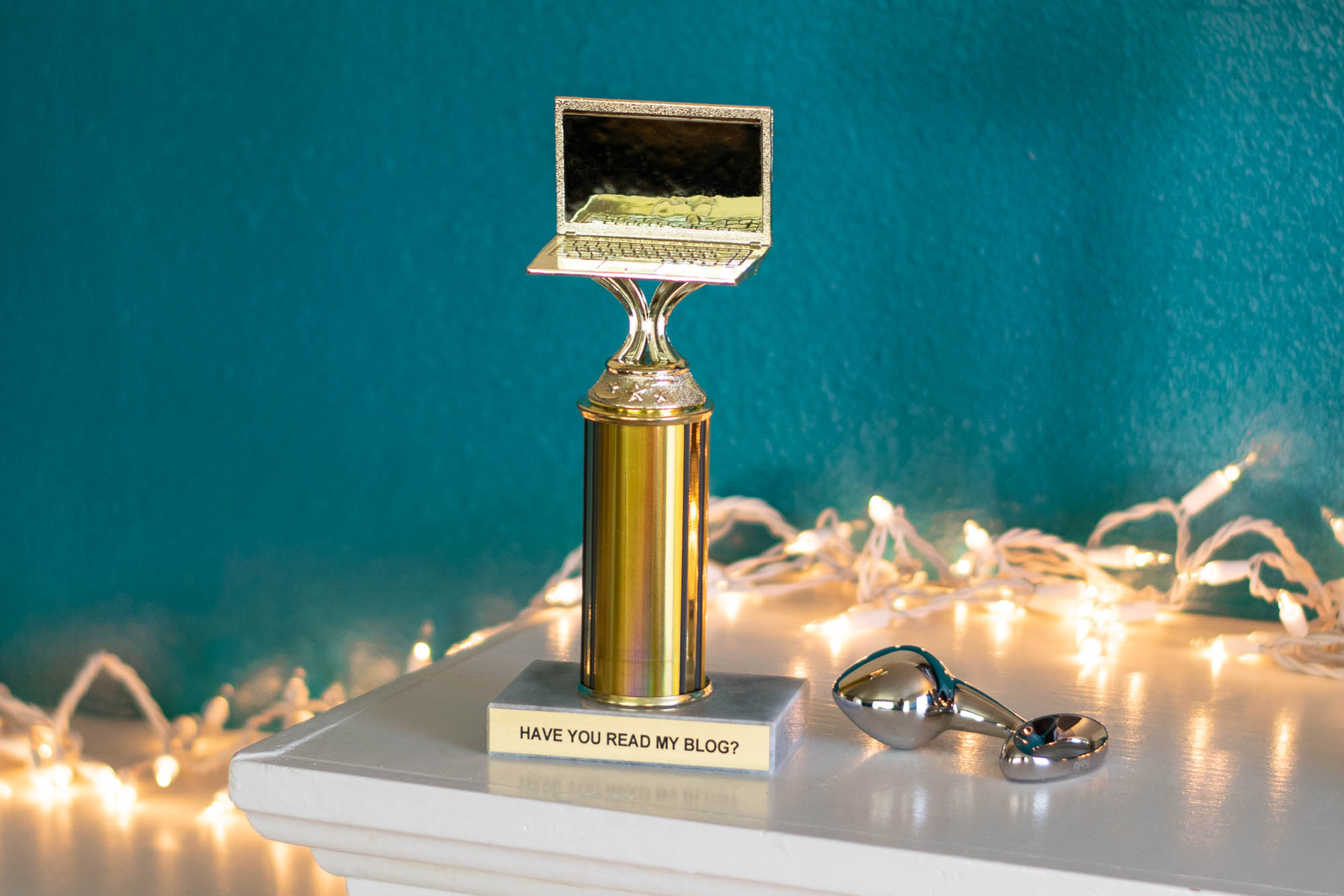 """A trophy with a laptop on top, which reads, """"HAVE YOU READ MY BLOG?"""" Next to it, a stainless steel butt plug."""