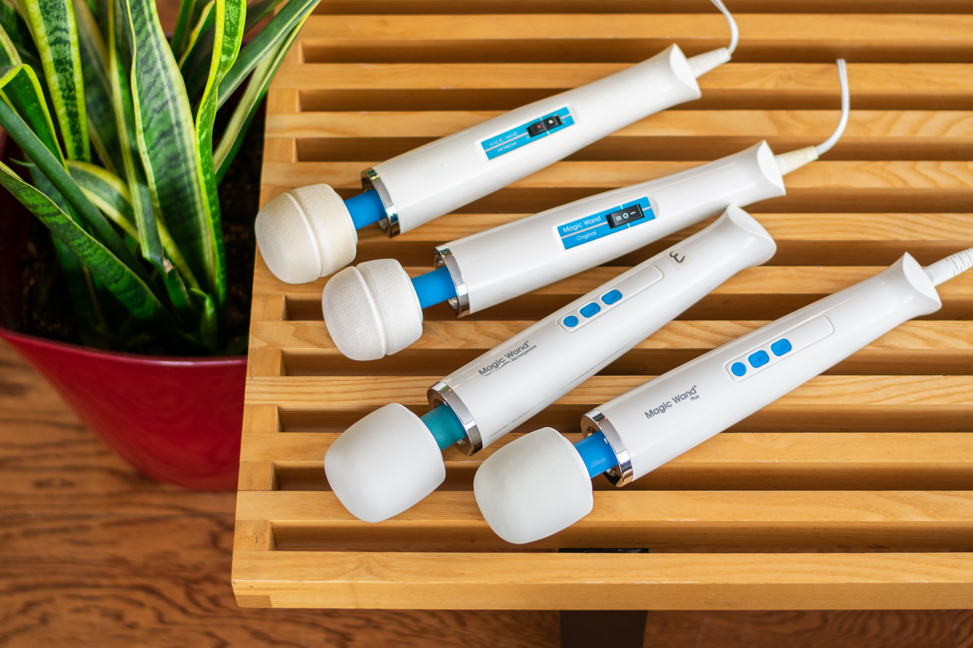 Four different iterations of the Hitachi Magic Wand vibrator, lying on top of a wooden bench near a green plant.