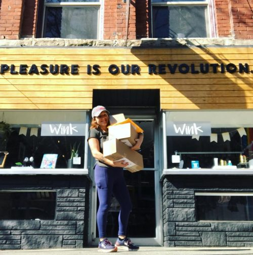 "Jenn Mason, owner of WinkWink, standing outside the shop holding a bunch of packages. The shop behind her reads, ""PLEASURE IS OUR REVOLUTION."""